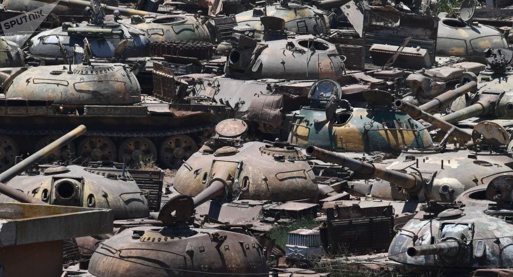 دبابات متضررة في الحرب بمصنع لتصليح المدرعات في ريف حمص، سوريا