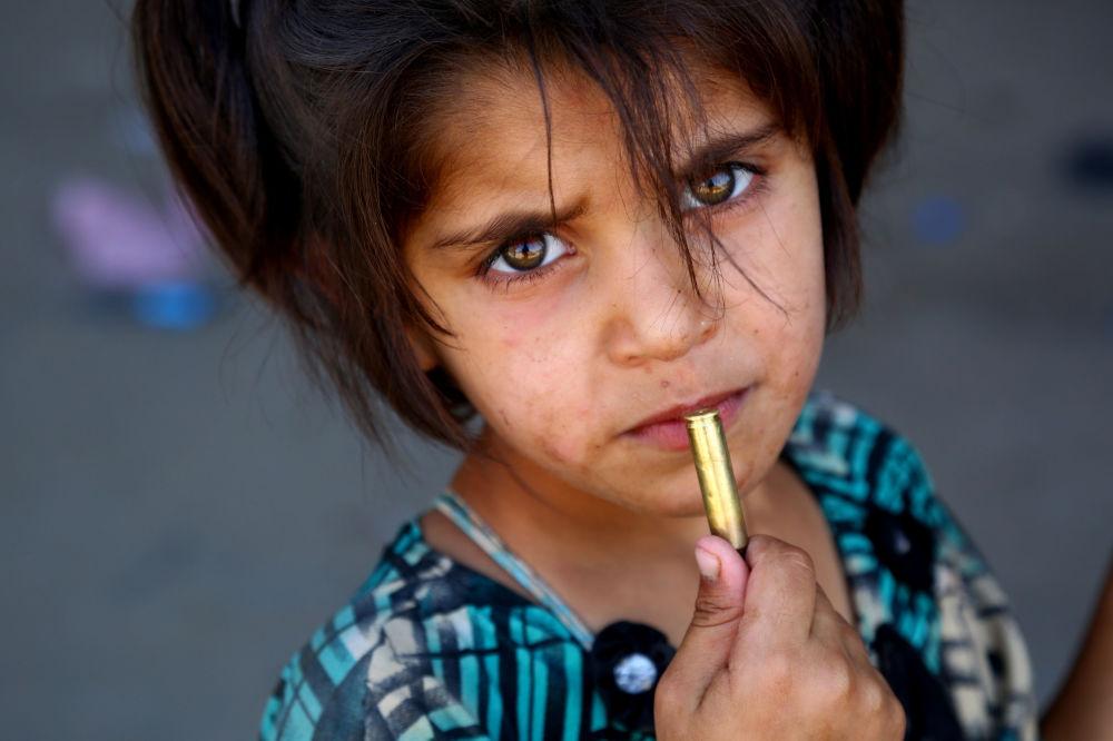 طفلة تمسك بيدها طلقة رشاش، بالقرب من مدينة الرقة السورية