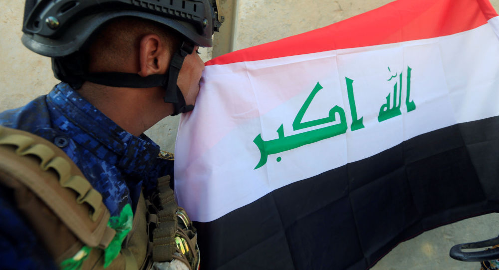أحد عناصر الشرطة العراقية يقبل العلم العراقي بعد تحرير الموصل، العراق 9 يوليو/ تموز 2017