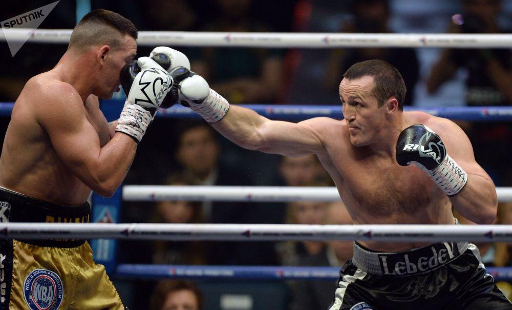 من الييمين إلى اليسار: الملاكمان الروسي دينيس ليبيديف والأسترالي مارك فلينغان خلال مباراة بطولة العالم للملاكمة المحترفة