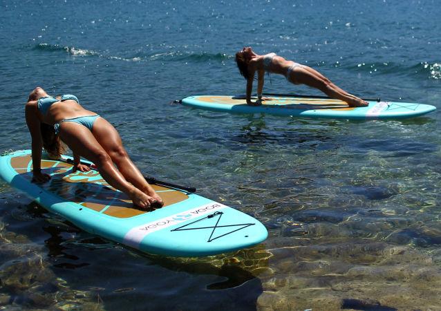 ممارسة اليوغا على ألواح الركمجة في فيروديلا على ساحل البحر الأدرياتيكي، كرواتيا 10 يوليو/ تموز 2017