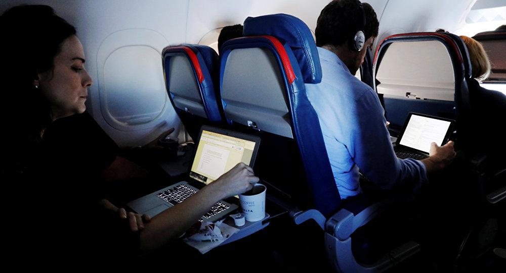 ركاب طائرة يستخدمون أجهزة محمولة