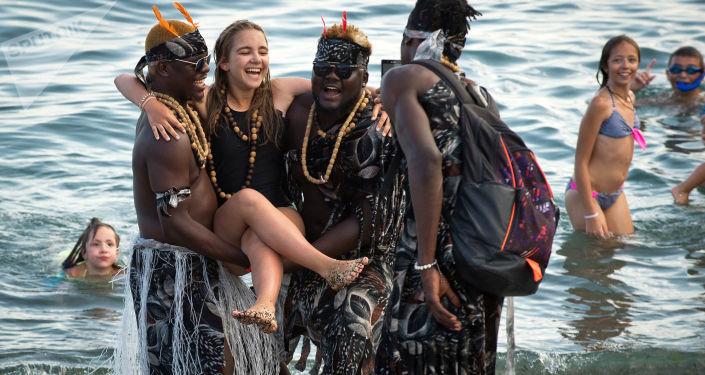 السياحة في القرم - فتاة أثناء التصوير مع سياح أجانب