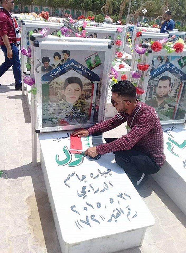 شاب عراقي أمام قبر أحد ضحايا داعش
