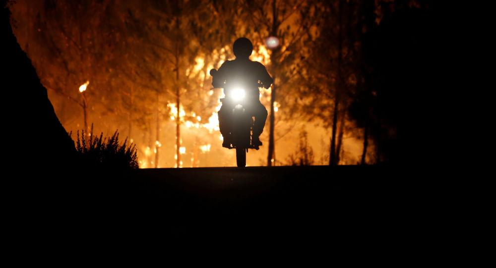 رجل الاطفاء راكبا دراجته النارية، يهرب بعيدا عن حريق الغابات المندلعة بالقرب من قرية ماكاو، بالقرب من كاستيلو برانكو، البرتغال 26 يوليو/ تموز 2017