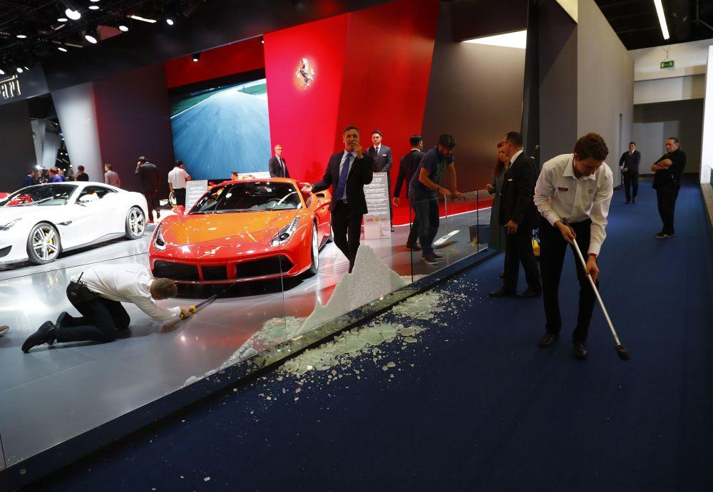 العاملين يفومون بمسح الأرض بعد تحطم لوحة الزجاج مكان موقف الفيراري في المعرض الدولي للسيارات في فرانكفورت، ألمانيا