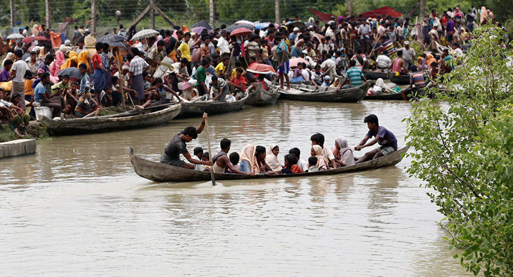 A boat carrying Rohingya refugees is seen leaving Myanmar through Naf river while thousands other waiting in Maungdaw, Myanmar, September 7, 2017