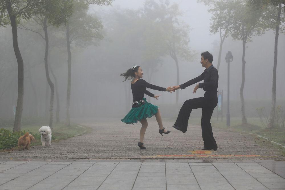 شخصان يرقصان في حديقة هوایان، الصين 10 أكتوبر/ تشرين الأول 2017