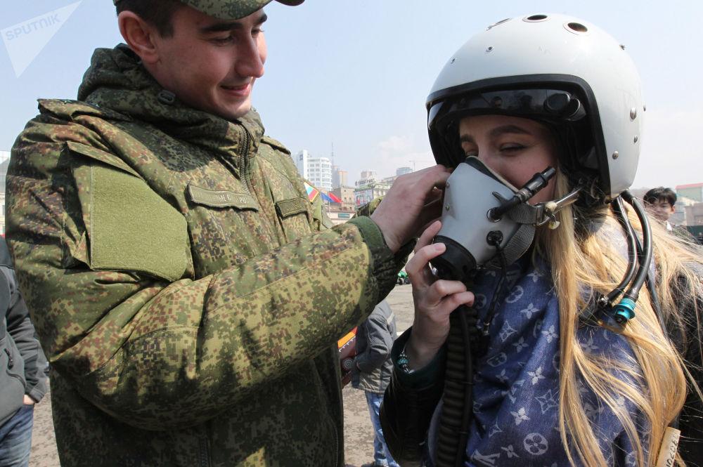 عسكري يساعد فتاة على ارتداء خوذة طيار خلال المعرض العسكري في فلاديفوستوك