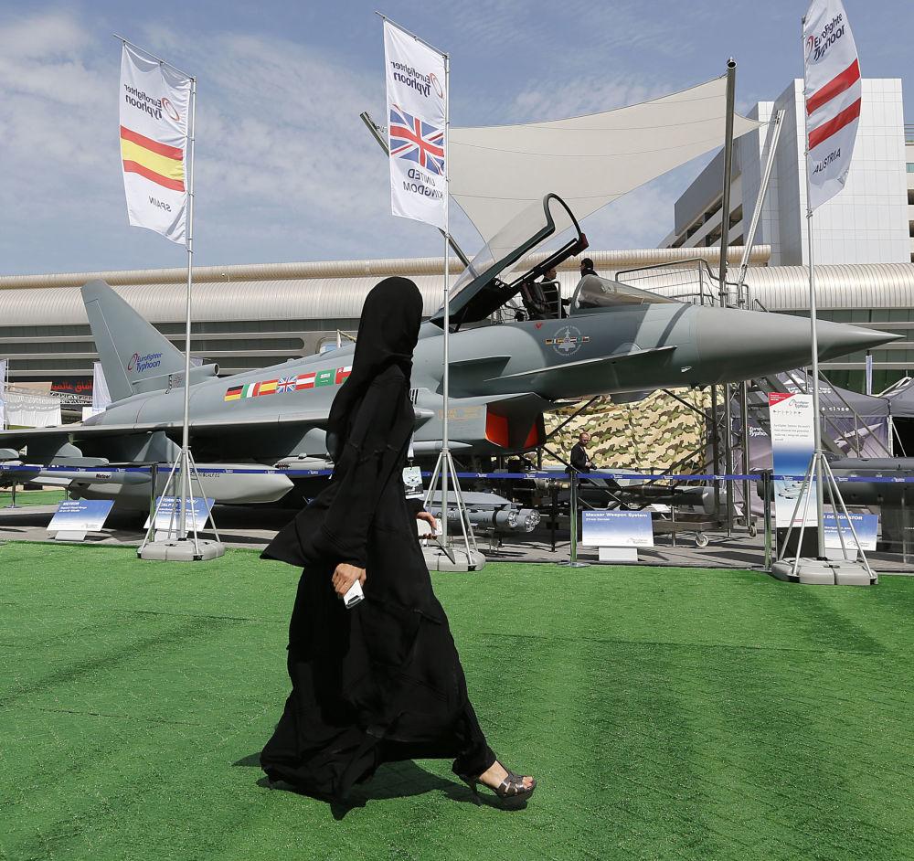 فتاة تسير على خلفية قاذفة Eurofighter Typhoon في المعرض العسكري IDEX  في الإمارات العربية المتحدة