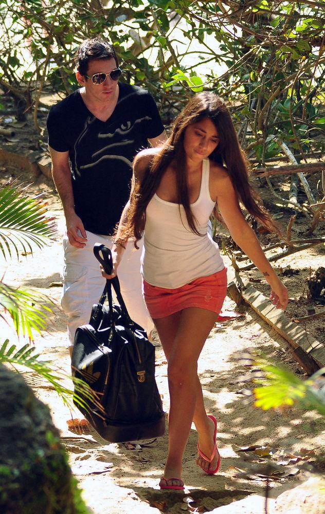 اللاعب الأرجنتيني ليونيل ميسي (برشلونة) وزوجته أنتونيللا روكوتزو، يغادران الشاطئ إثر وصول الصحفيين، ريو دي جانيرو 9 يوليو/ تموز 2017