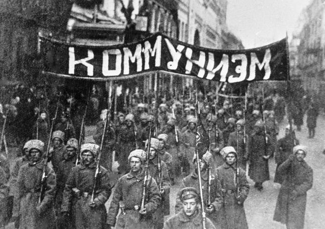 ثورة أكتوبر عام 1917 - مجموعات من الجنود الثوريين يحملون شعار كومونيزيم (الشيوعية) يسيرون في شارع نيكولسكايا في موسكو، عام 1917