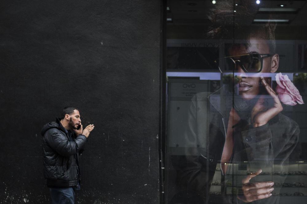 رجل يتحدث على الهاتف المحمول على خلفية صورة إعلانية في نيويورك، الولايات المتحدة 14 نوفمبر/ تشرين الثاني 2017