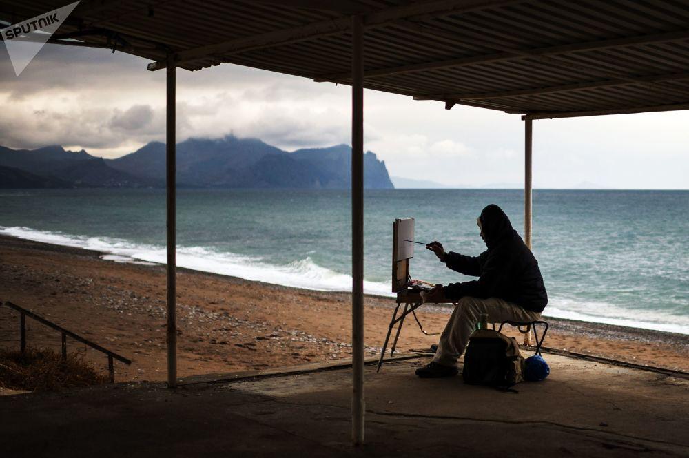 فنان يرسم على أحد شواطئ سيفاستوبل، القرم، روسيا