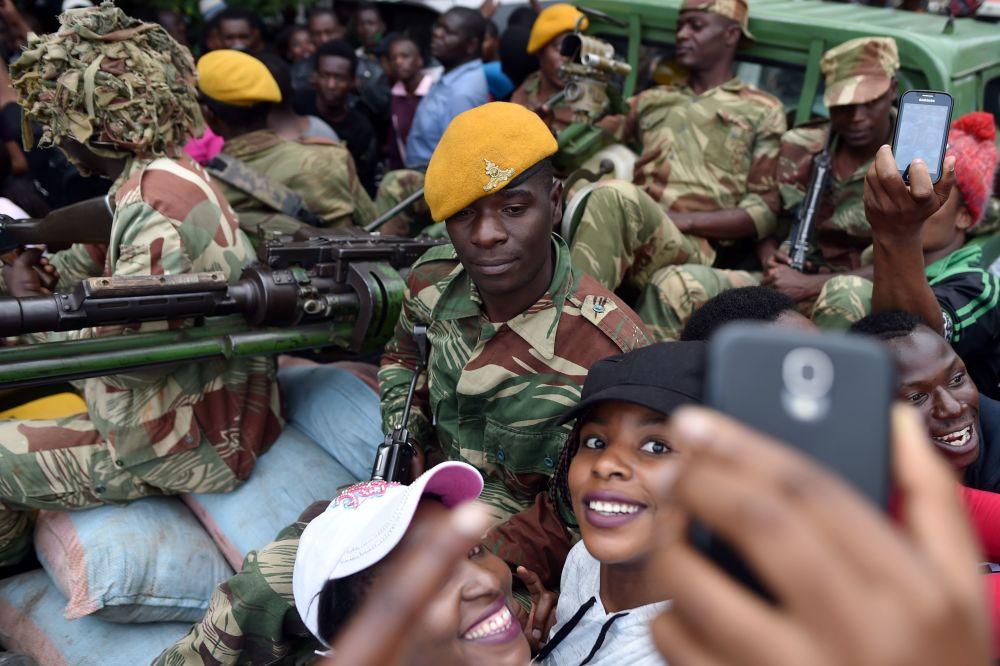 فتيات يلتقطن صورة سيلفي على خلفية جنود من الجيش الوطني في هراري، زيمبابوي 18 نوفمبر/ تشرين الثاني 2017