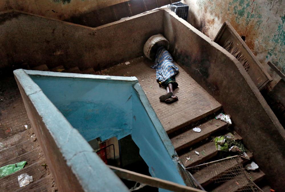 متسول ينام على الدرج في سوق الجملة في بنغالور، الهند