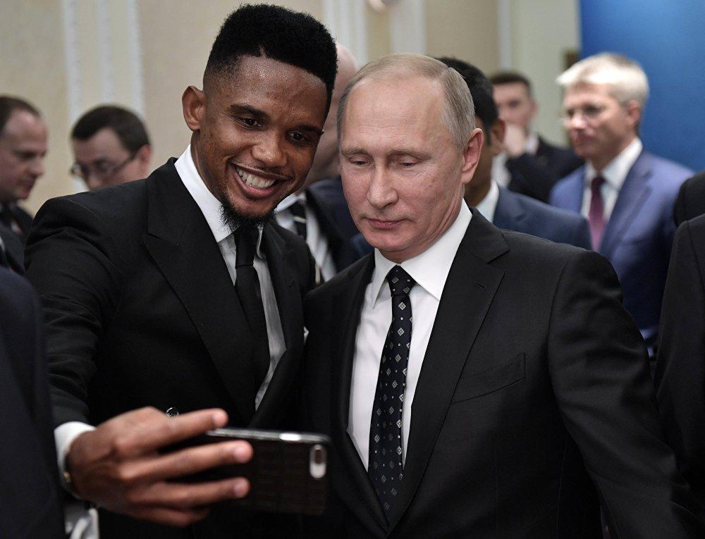 الرئيس الروسي فلاديمير بوتين واللاعب الكاميروني السابق صامويل إيتو