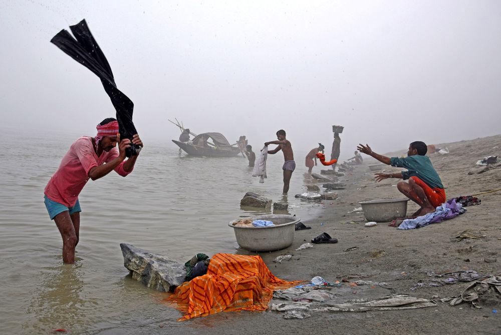 الناس يغسلون الملابس على ضفاف نهر براهمابوترا في صباح الشتاء الضبابي في غواهاتي، الهند، 4 ديسمبر/ كانون الأول 2017