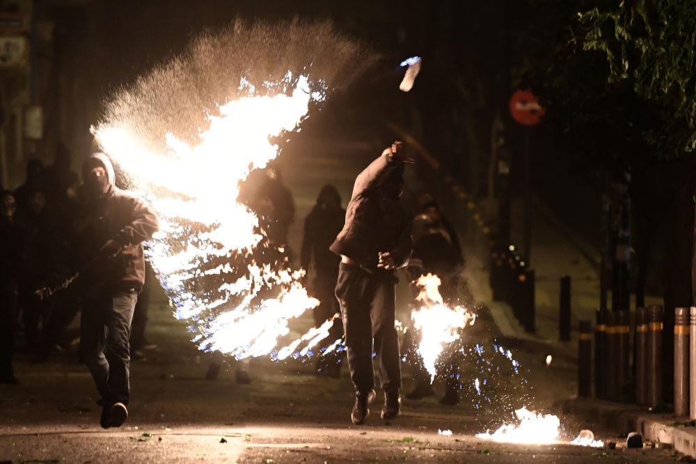 متظاهر يقذف بزجاجة بنزين على موقع للشرطة  في أثينا، اليونان 6 ديسمبر/ كانون الأول 2017