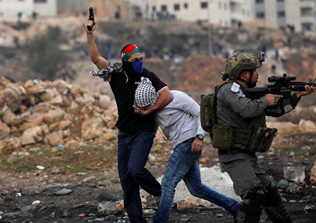 احتجاز أحد عناصر الأمن الإسرائيلي لأحد الفلسطينيين المتظاهرين خلال الاحتجاجات ضد قرار الرئيس دونالد ترامب بالاعتراف بالقدس عاصمة لاسرائيل، بالقرب من مستوطنة بيت إيل اليهودية، بالقرب من مدينة رام الله بالضفة الغربية فى 13 ديسمبر/ كانون الأول عام 2017.