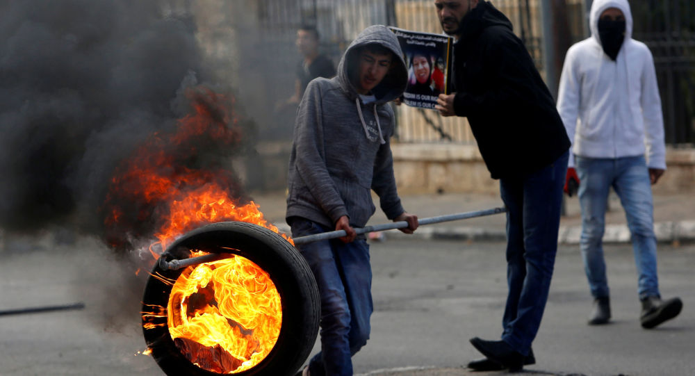 فلسطيني يحمل إطارا مشتعلا خلال المواجهات مع الشرطة الإسرائيلية في بيت لحم، الضفة الغربية، فلسطين 27 ديسمبر/ كانون الأول 2017