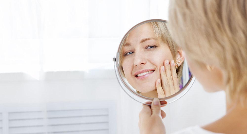 فتاة تنظر في المرآة
