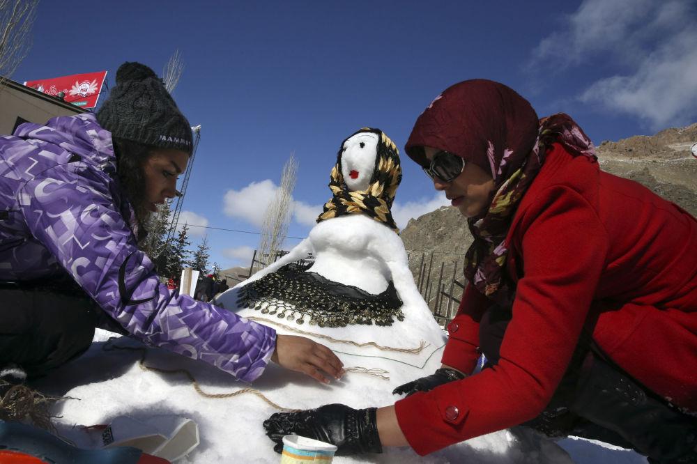 نساء يصنعون تماثيلا من الثلج أثناء مهرجان رجل الثلج في إيران