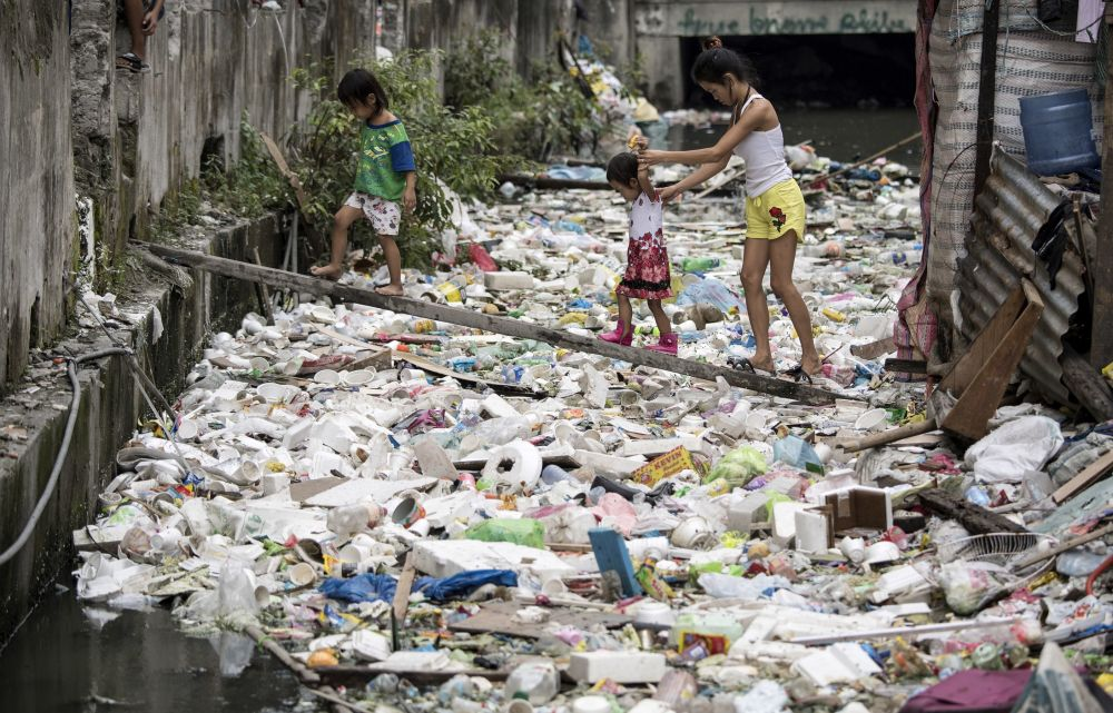 محليون يسيرون على لوح خشبي لعبور الممر المائي والقمامة في مانيلا 17 يناير/ كانون الثاني 2018