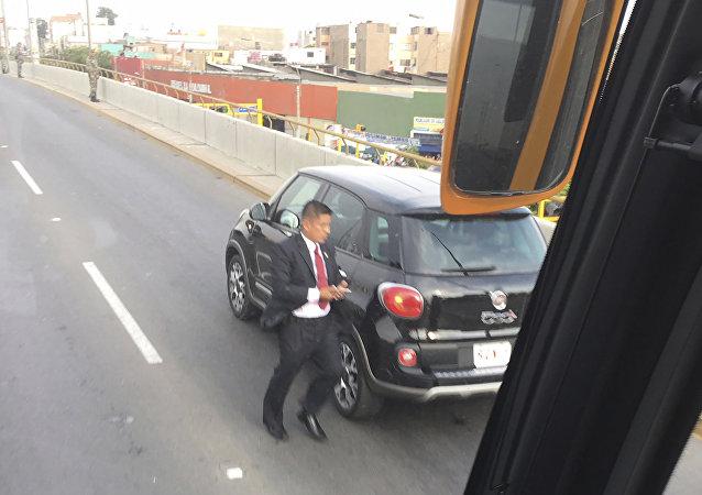 رجل يندفع حول السيارة التي تحمل البابا فرانسيس، بعد أن توقفت على الطريق مع الإطارات المسطحة، في الطريق إلى قصر الحكومة في ليما، بيرو، الجمعة، 19 يناير/كانون الثاني 2018.