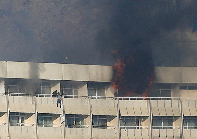 رجل أفغاني يحاول الخروج من فندق بكابول بعد هجوم عليه