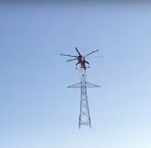 هليكوبتر تطير بعمود كهرباء