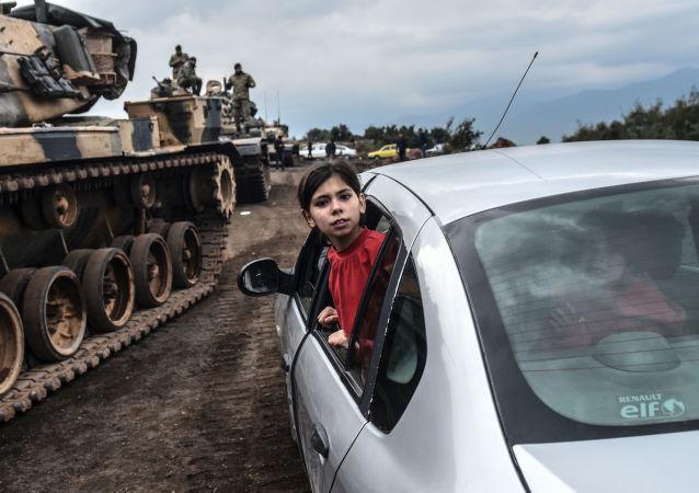 طفلة تركية تنظر عبر نافذة سيارة على خلفية تجمع لدبابات الجيش التركي على الحدود السورية التركية في هاتاي، 21 يناير/ كانون الثاني 2018
