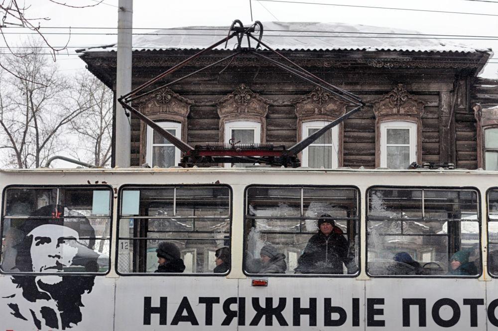 حافلة عليها إعلان على خلفية منزل قديم في إركوتسك