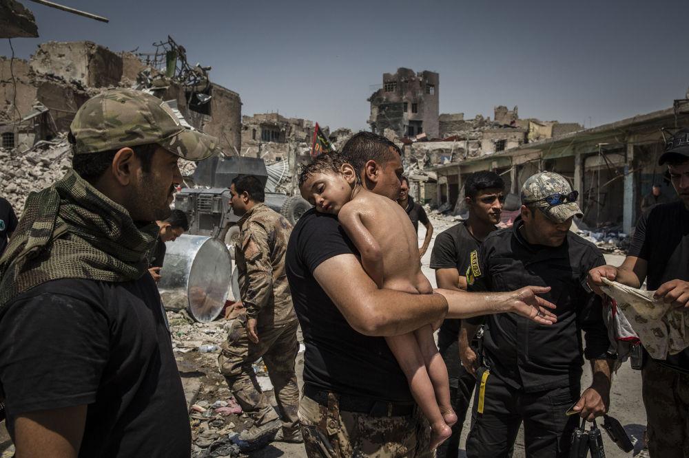 مسابقة صورة الصحافة العالمية لعام 2018 - صورة بعنوان معركة تحرير الموصل - أفراد القوات الخاصة العراقية يعتنون بالصبي للمصور إيفور بريكيت، في فئة التصوير صورة الصحافة العالمية لهذا العام