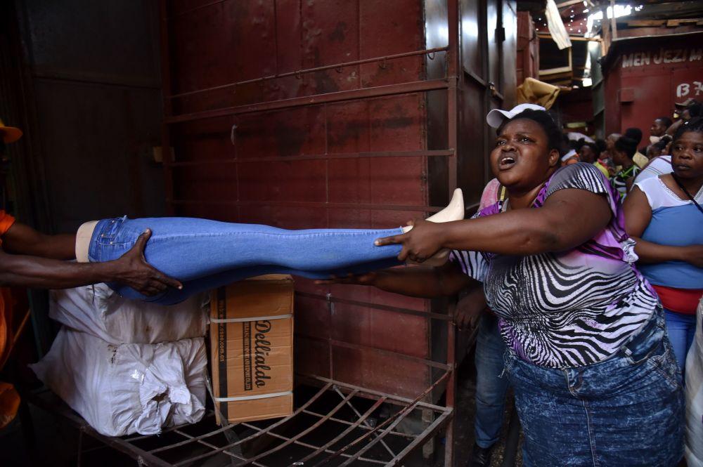 بائعون يحاولون انقاذ بضائعهم من الحريق الذي اشتعل في أحد أسواق مدينة بورت-أو-برينس، 18 فبراير/ شباط 2018
