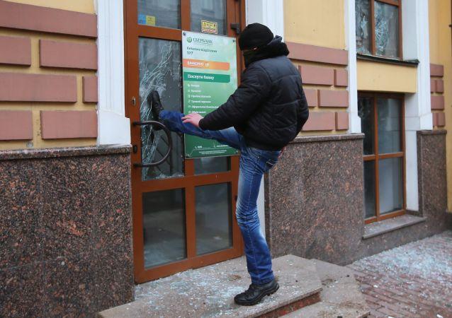 أحد المحتجين يحاول كسر باب بنك سبيربانك الروسي في كييف، أوكرانيا