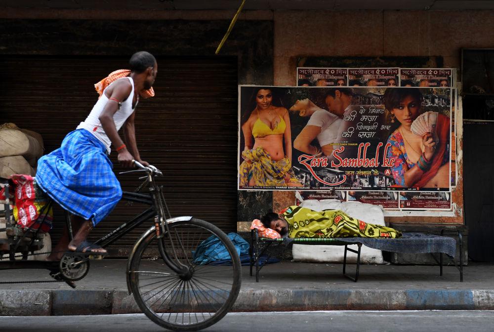 رجل يركب دراجة هوائية على خلفية لوحة إعلانات للسينما في كلكتا، الهند 12 مارس/ آذار 2018