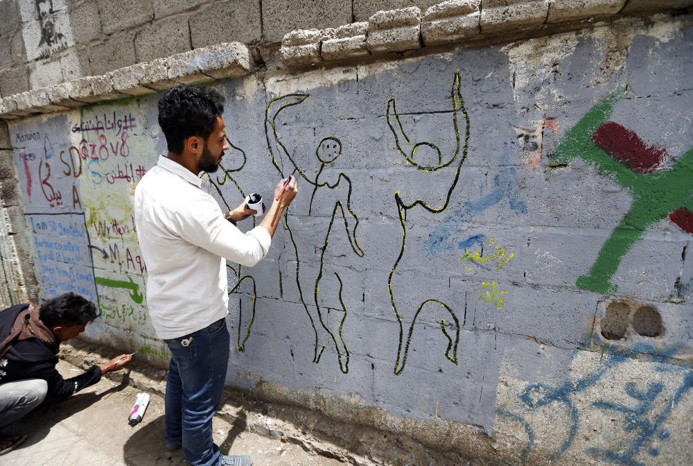 فنان يمني يرسم لوحة غرافيتي على الجدران لدعم السلام، في إطار حملة يوم مفتوح للفن في العصامة صنعاء، اليمن 15 مارس/ آذار 2018