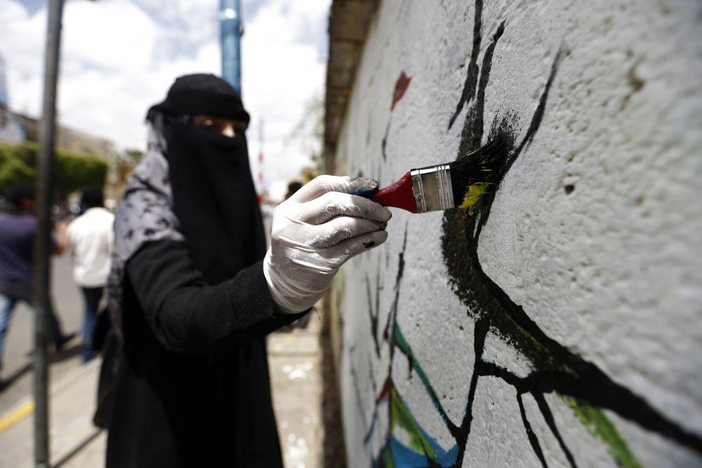 فنانة يمنية ترسم لوحة غرافيتي على الجدران لدعم السلام، في إطار حملة يوم مفتوح للفن في العصامة صنعاء، اليمن 15 مارس/ آذار 2018