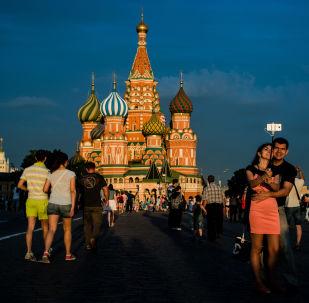 أشخاص يلتقطون صورة سيلفي على خلفية كتدرائية القديس باسيل على الساحة الحمراء بموسكو