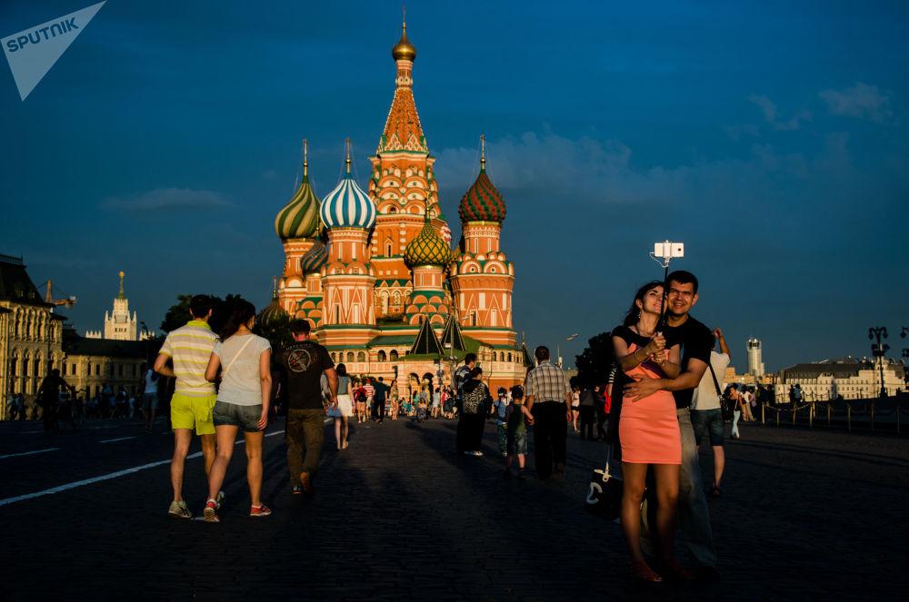 أشخاص يلتقطون صورة سيلفي على خلفية كتدرائية القديس باسل على الساحة الحمراء بموسكو