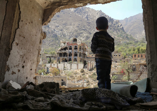 صبي صغير يقف على خلفية ركام في تعز، اليمن 18 مارس/ آذار 2018