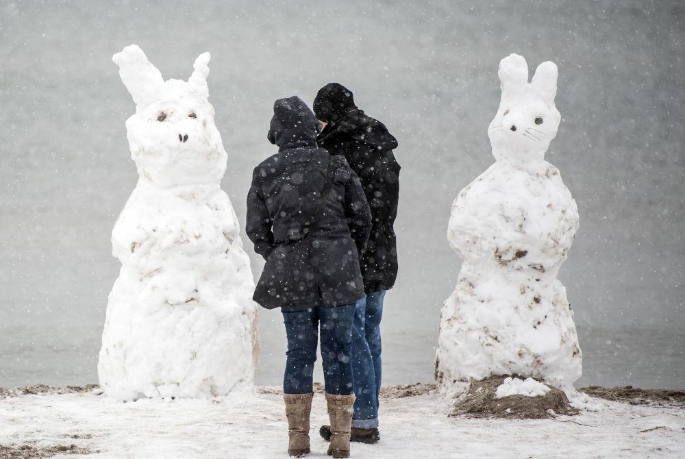 شخصان يقفان بالقرب من رجال ثلج على شكل أرنب في جزيرة فيرمان، ألمانيا 1 أبريل/ نيسان 2018