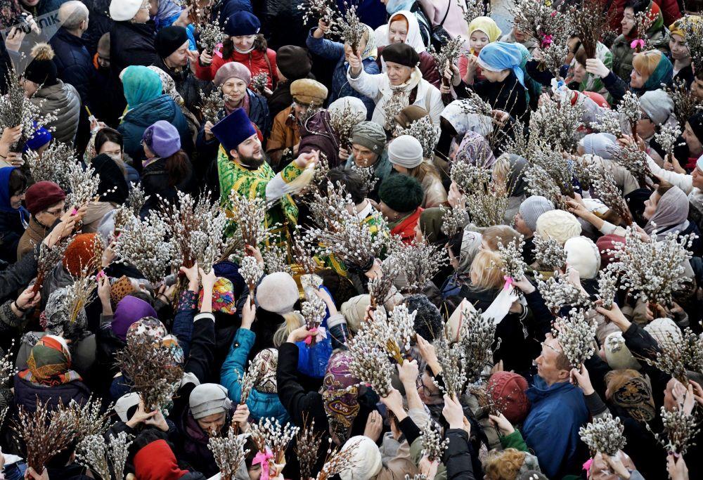 الكاهن والمصلون خلال مراسم الاحتفال بأحد الشعانين - دخول يسوع إلى مدينة القدس - في كاتدرائية سباسو بري أوبراجينسكي في خاباروفسك، روسيا