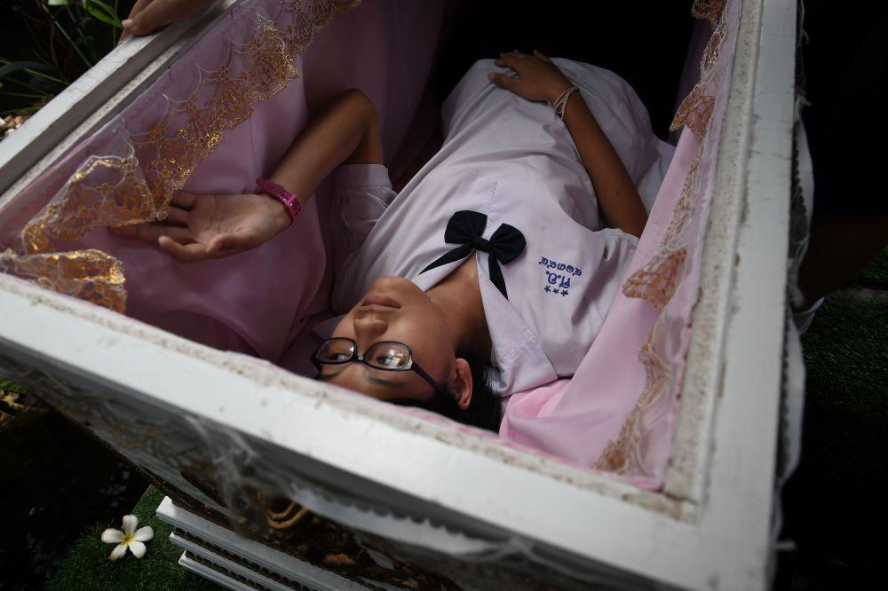 مراهقة تجرب تابوتا تقليديا في مقهى كيد ماي ديث أويرنيس ( Kid Mai Death Awareness) في بانكوك، ويهدف إلى نشر الوعي حول الموت والبوذية، 30 مارس/ أبريل 2018
