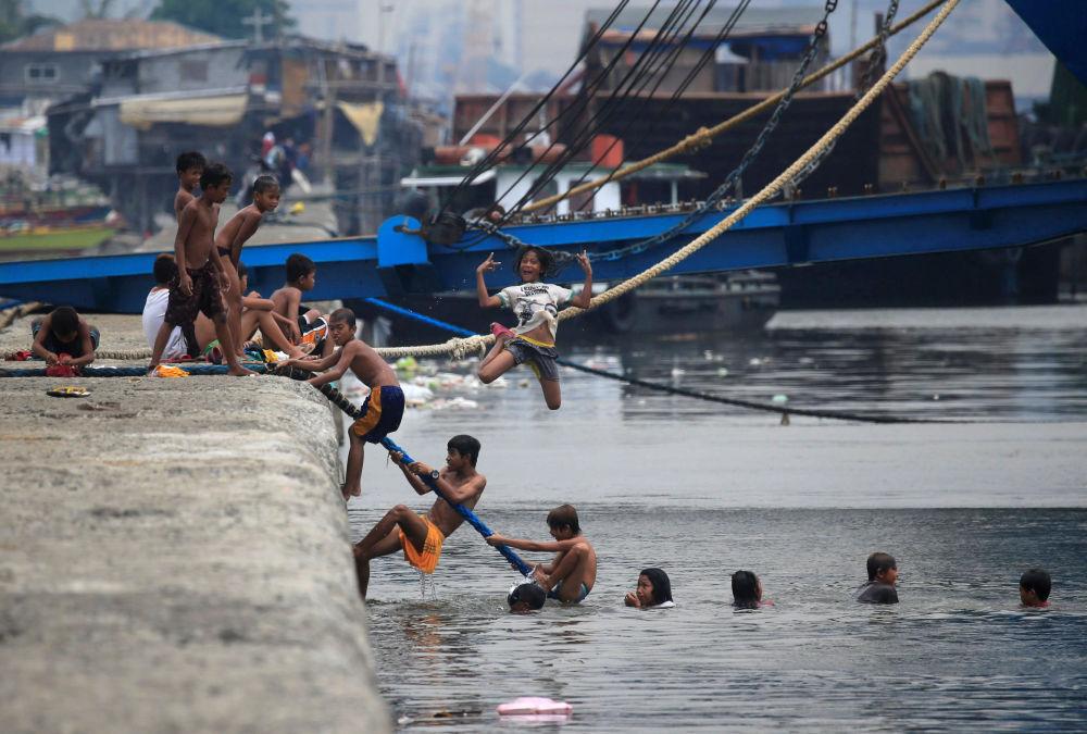 أطفال يقفزون إلى مياه خليج مانيلا هروبا من الحر، الفلبين 11 أبريل/ نيسان 2018