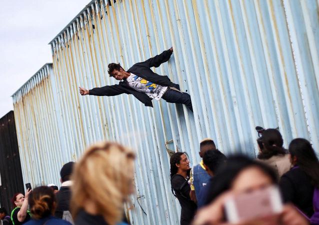رجل يتسلق السياج الحدودي بين المكسيك والولايات المتحدة كجزء من المظاهرة، حيث يجتمع أعضاء من قافلة المهاجرين من أمريكا الوسطى قبل الاستعدادات لطلب اللجوء في الولايات المتحدة ، في تيخوانا، المكسيك 29 أبريل/ نيسان 2018