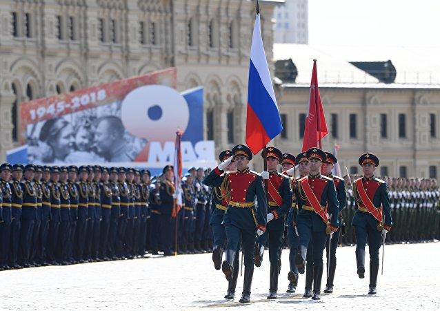 تمر على أرصفة الساحة الحمراء، راية النصر الإسطورية وعلم روسيا الاتحادية.