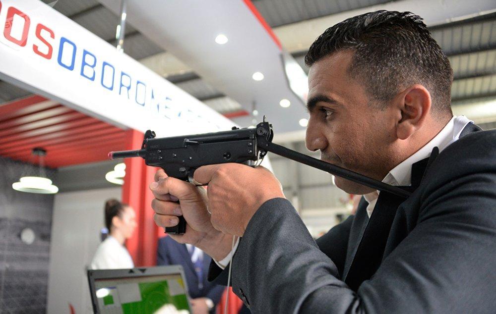 معرض قوات العمليات الخاصة سوفكس 2018 في القاعدة الجوية ماركا في الأردن - أحد زوار المعرض يجرب جهاز لمحاكاة البندقية الإلكترونية SCATT WM9 في جناح الشركة الروسية  روس أوبورون إكسبرت
