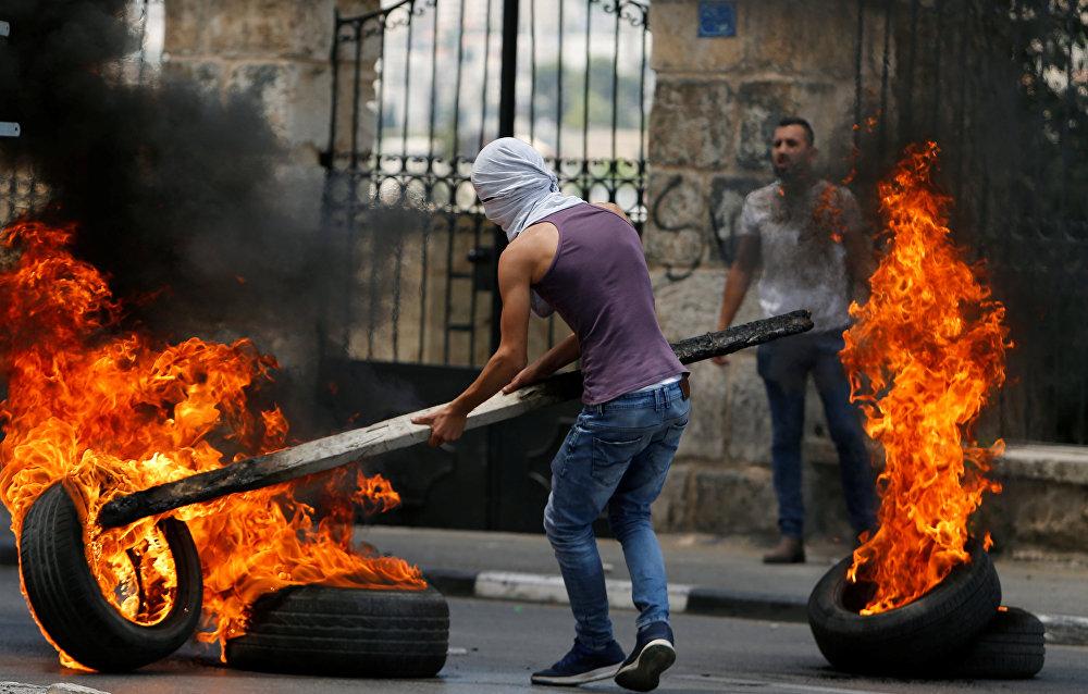 شبان فلسطينيون في بيت لحم، خلال احتجاجات ضد نقل السفارة الأمريكية إلى القدس عشية الذكرى الـ 70 للنكبة، الضفة الغربية، فلسطين 14 مايو/ أيار 2018
